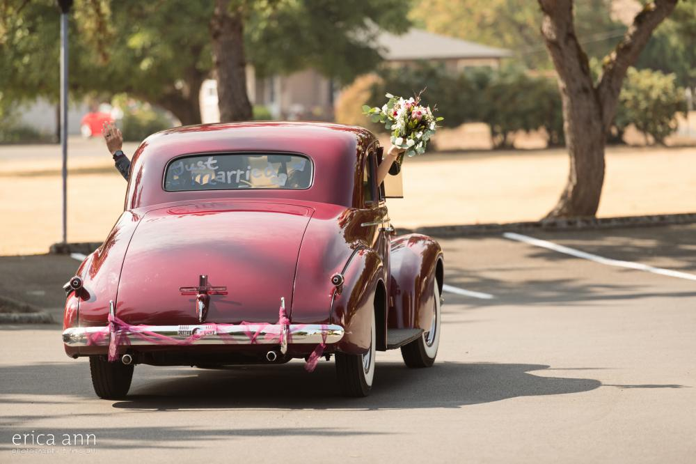 bride and groom classic getaway car